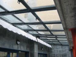 Techo motorizado en vidrio cámara 3+3/6/4 entre paredes con toldo plano.
